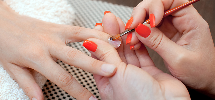 A closeup of a manicurist preparing acrylic nails