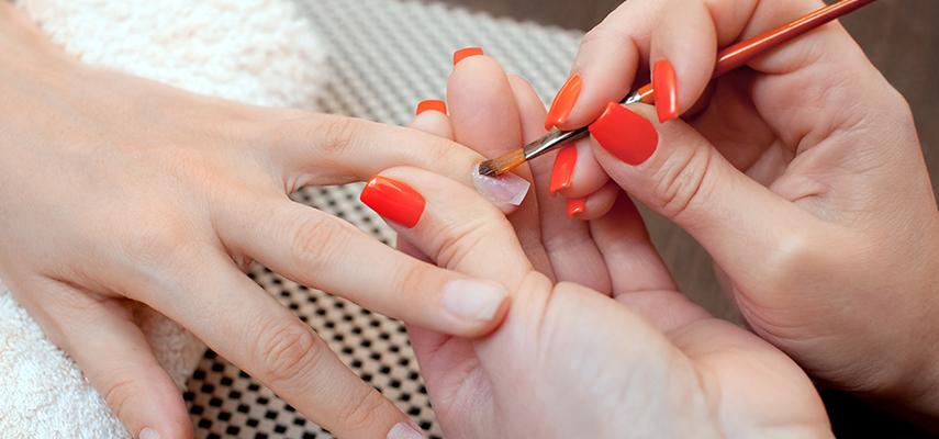 A closeup of a manicurist preparing acrylic nails