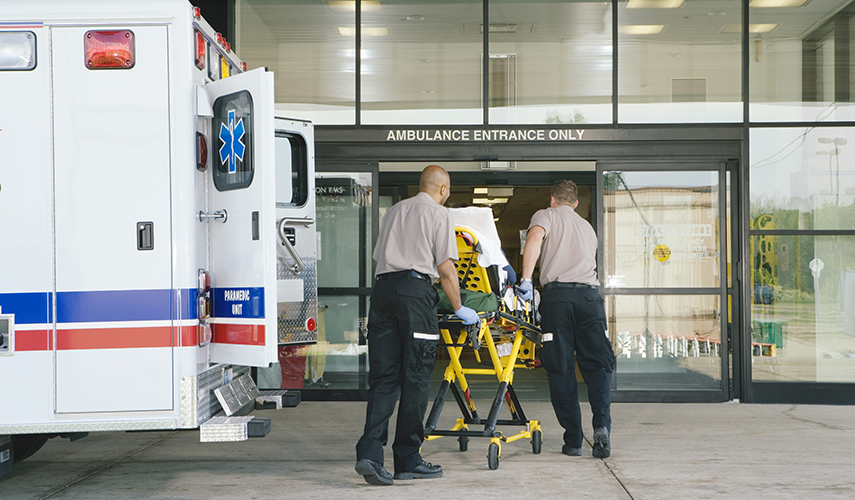 Two ambulance workers roll a stretcher into the entrance of a hospital