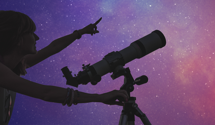 female student pointing at a purple sky with stars while standing by a large microscope