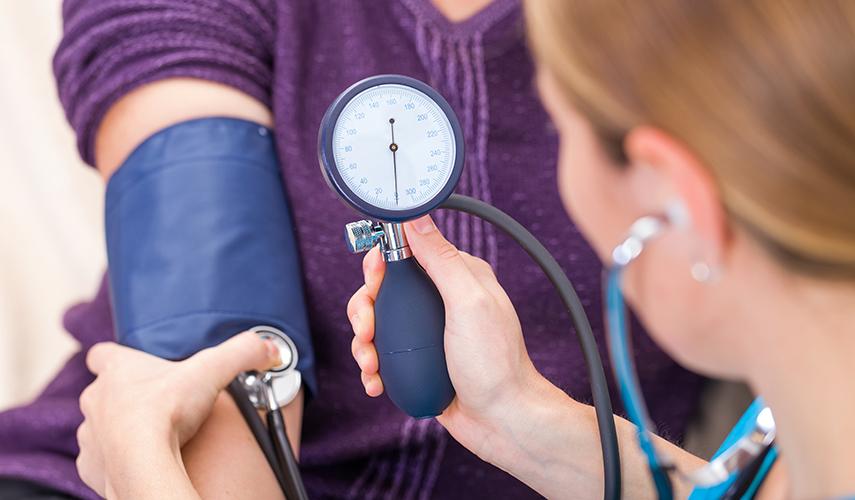 A medical assistant takes a patient's blood pressure measurement