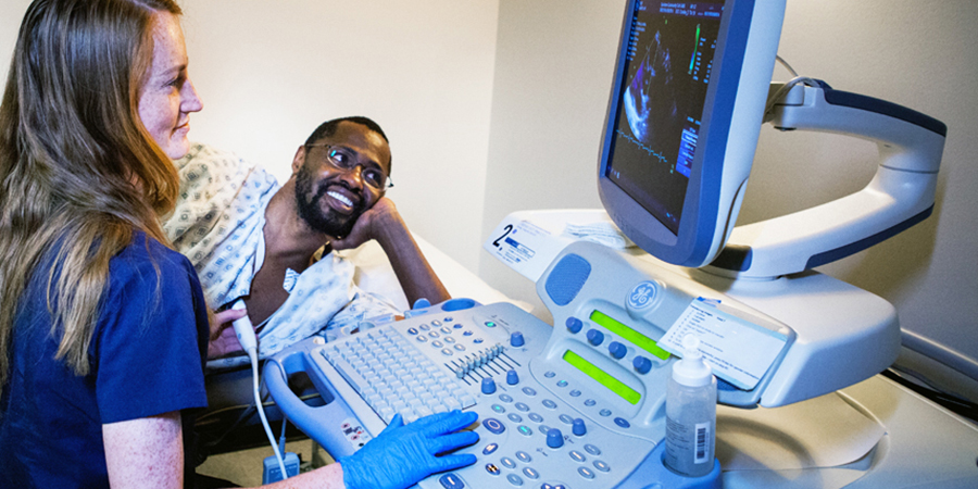 A student holds an ultrasound transducer in one hand while looking at a monitor