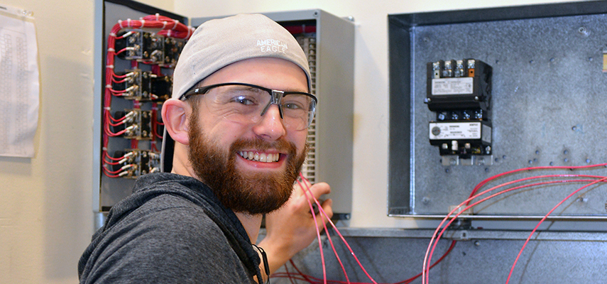 A student works with electrical equipment on the wall in a lab