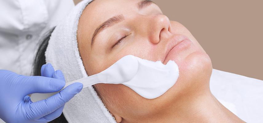 An esthetician applies a facial mask on a client