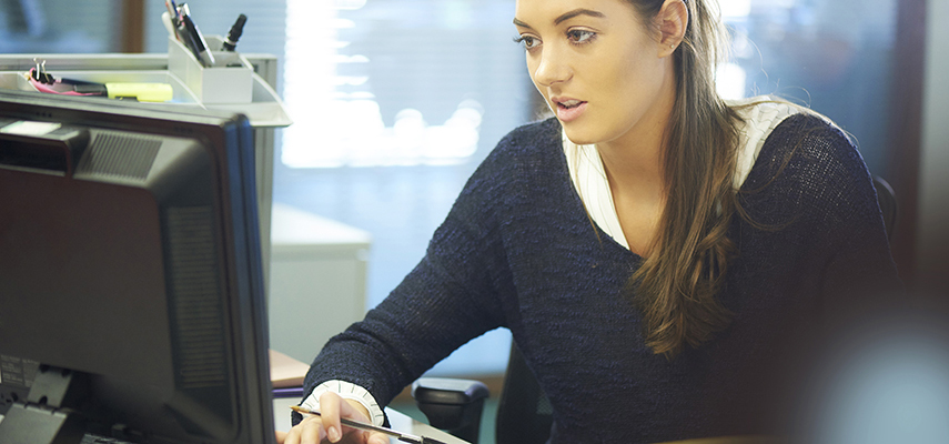 A young woman works on a computer in an office