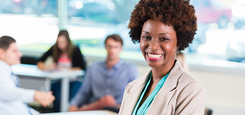 A smiling woman wearing a business suit stands near her colleagues at work