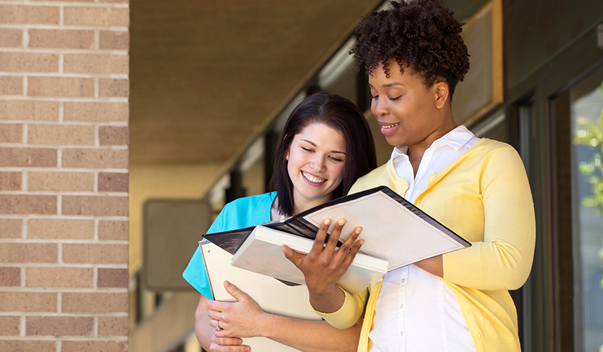 A nurse and a legal professional look at files together