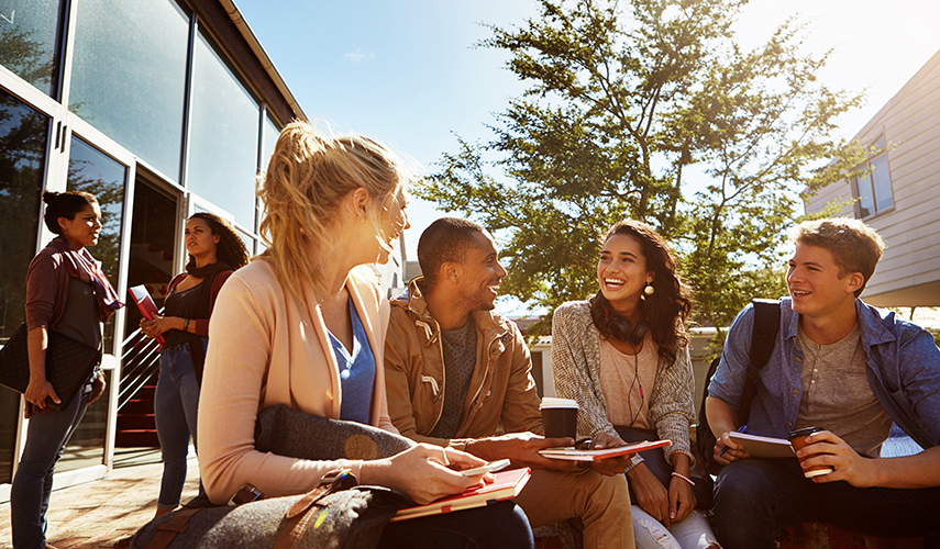 A group of students sit around talking outside
