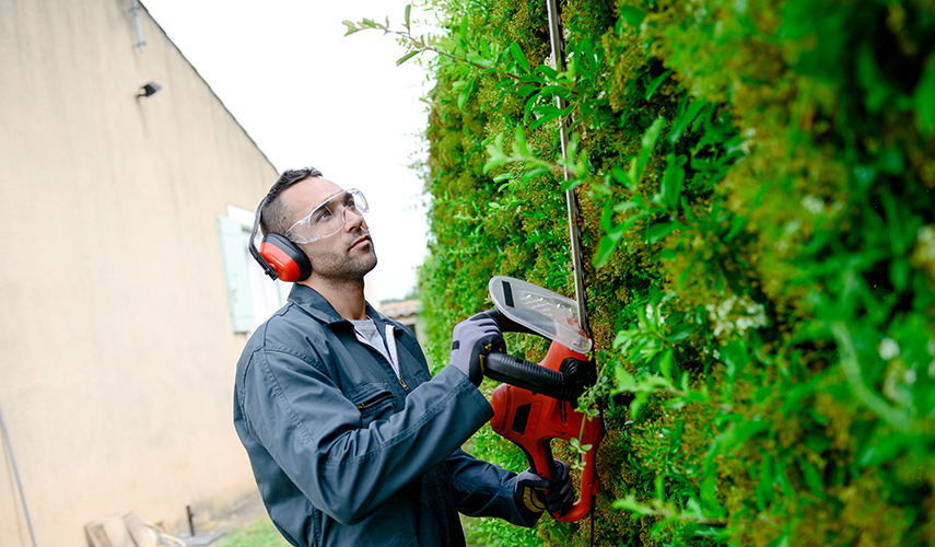 A landscaper trims bushes