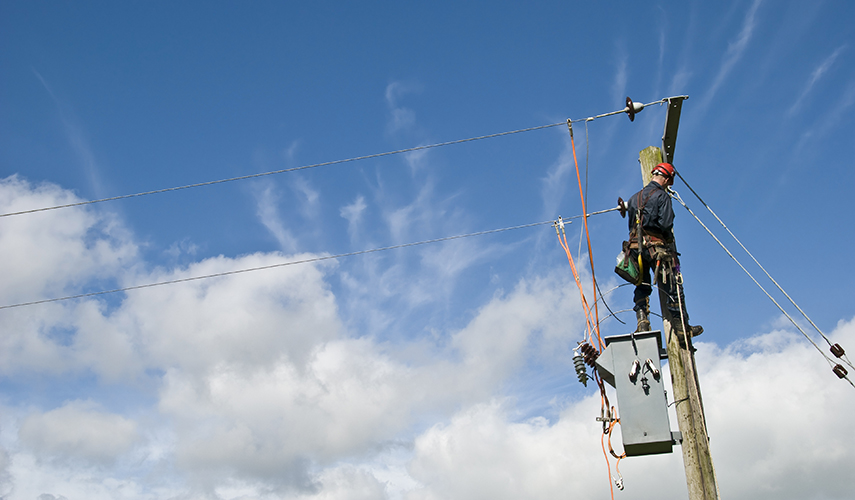 A lineman works on a powerpole