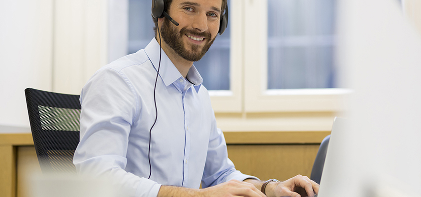 A young man wearing a headset works at a computer in an office