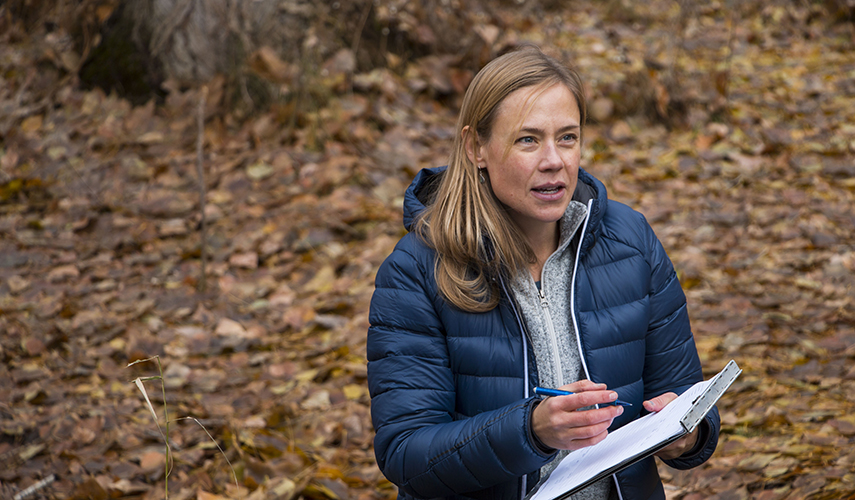 A woman conducts research outdoors