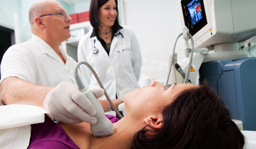 A male sonographer uses ultrasound to look at a woman's thyroid