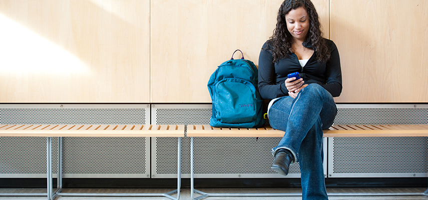 Student SItting on a bench in the hall - looking on her phone.