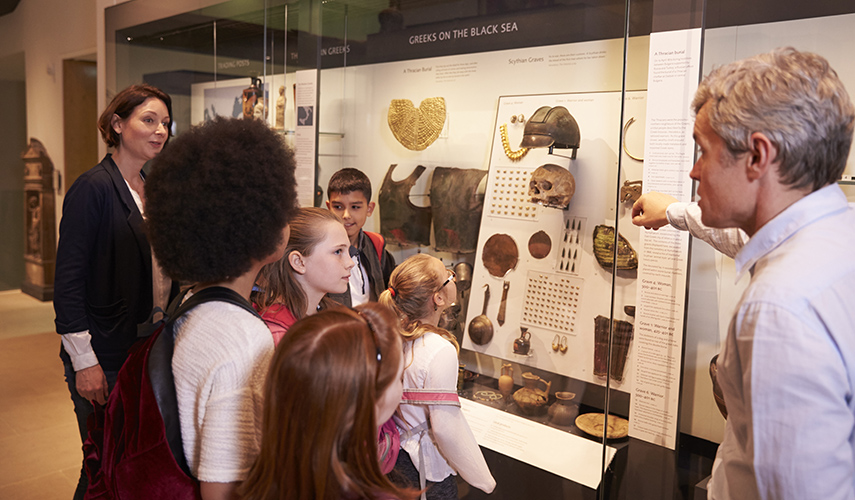 An anthropologist teaches a group of children about Greek artifacts in a museum