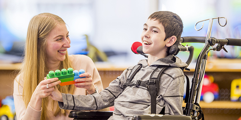 A paraprofessional plays blocks with a child in a wheelchair