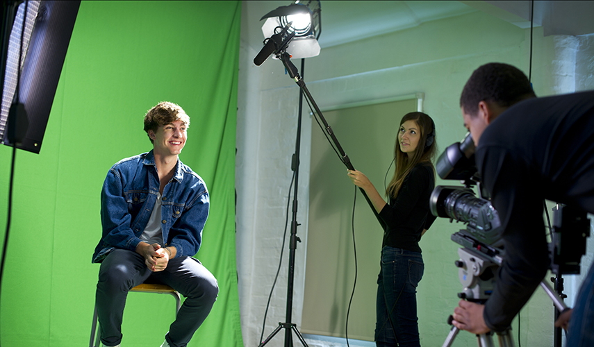 A male sits in front of a green screen while other students film and record him