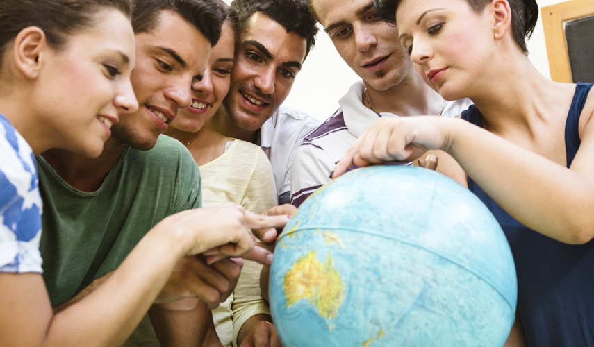 Students gathered around a globe pointing at a country