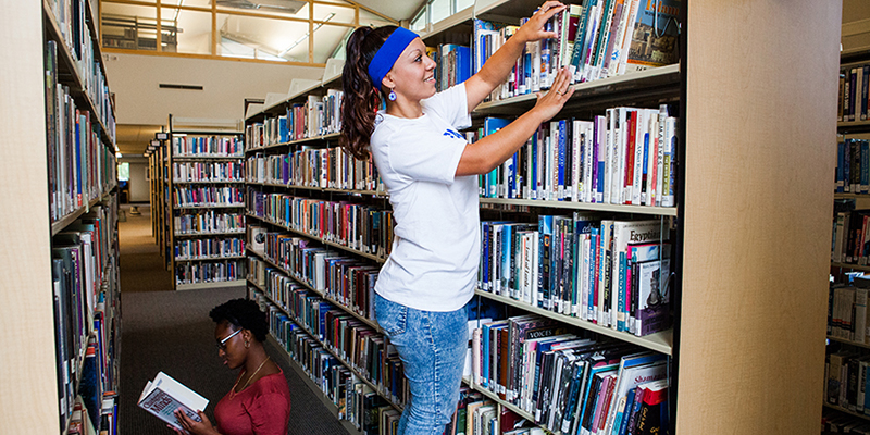 Two young women place books on the shelves of the campus library