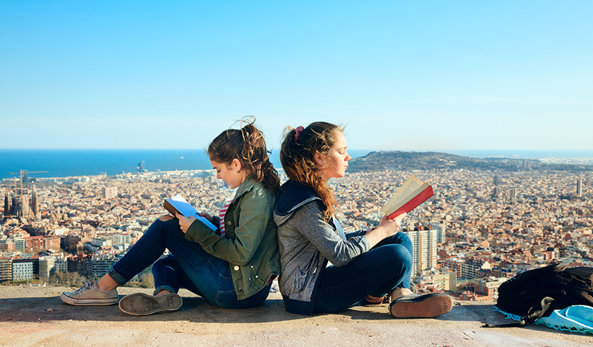 Two girls sitting atop a hill studying Spanish in Barcelona