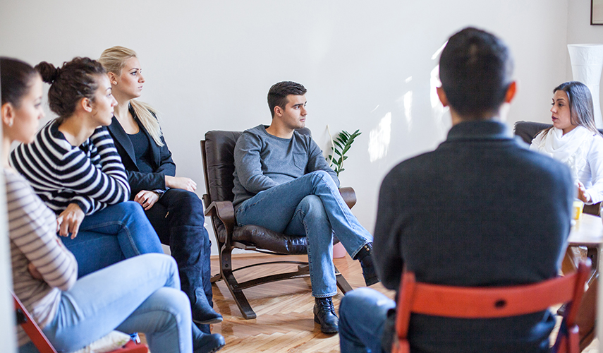 Members of a group therapy session pay attention to a speaker