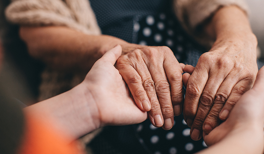 A closeup of young hands holding elderly hands