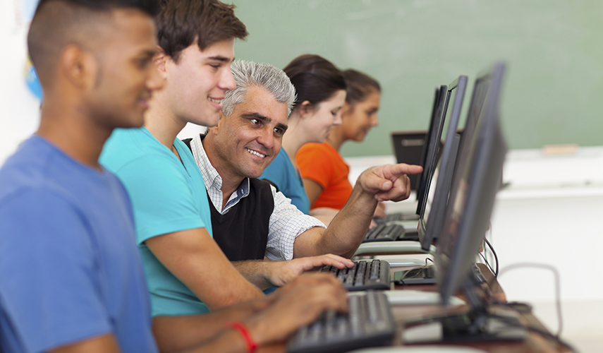 A teacher shows his student how to do something on the computer