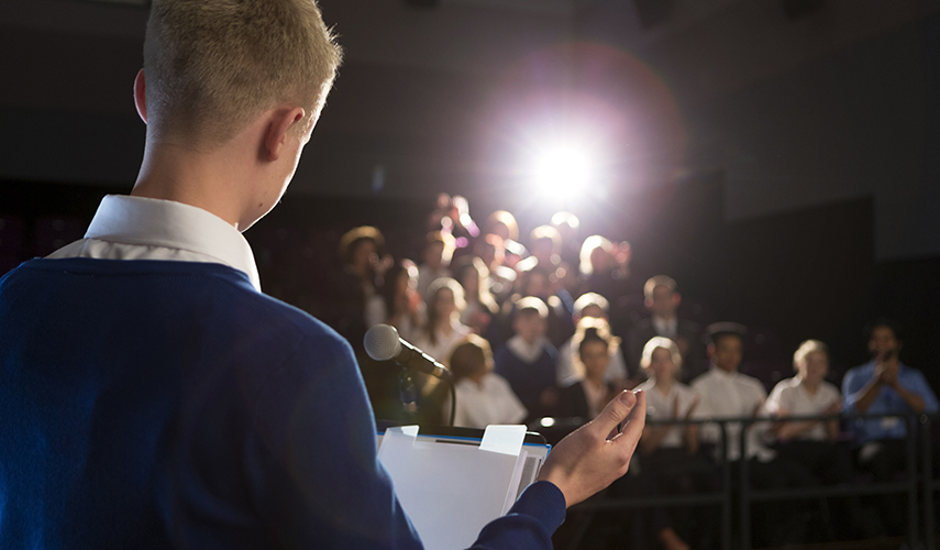 A male student gives a speech to a room full of people