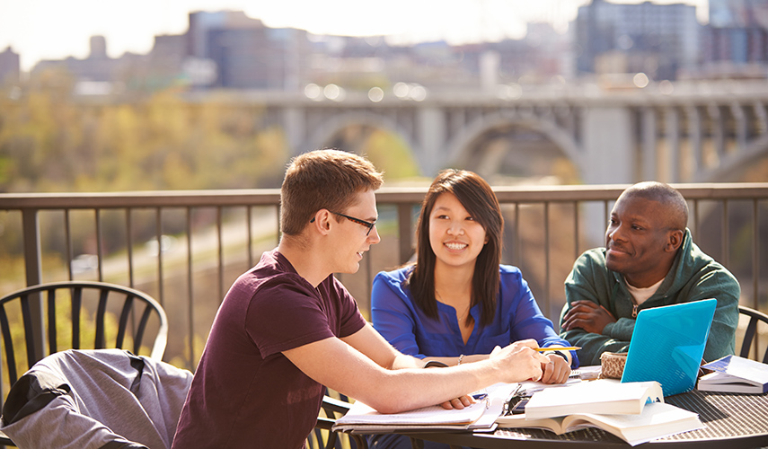 A group of students work and talk together at an outdoor table with the Monroe Street Bridge in the background