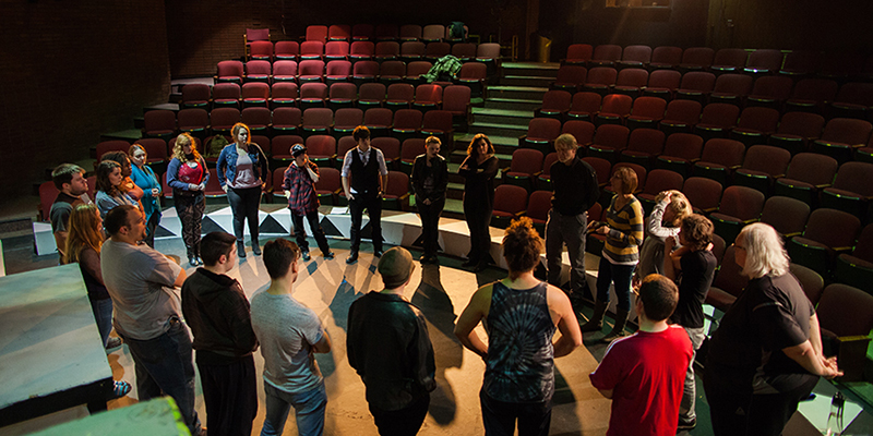 A group of students stand in a circle onstage, listening to the drama instructor