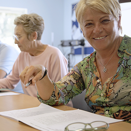 A Middle aged woman in the class croom, smiling