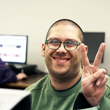 A male student giving the peace sign and smiling