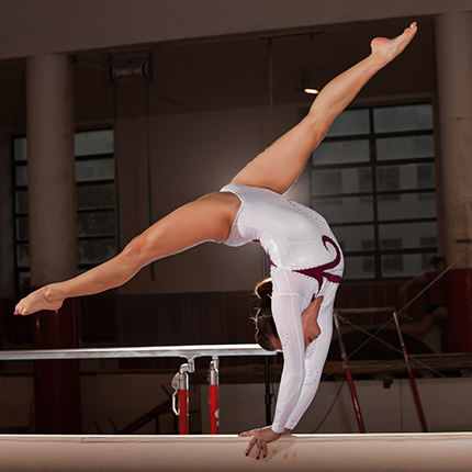 gymnast doing a handstand on the highbeam