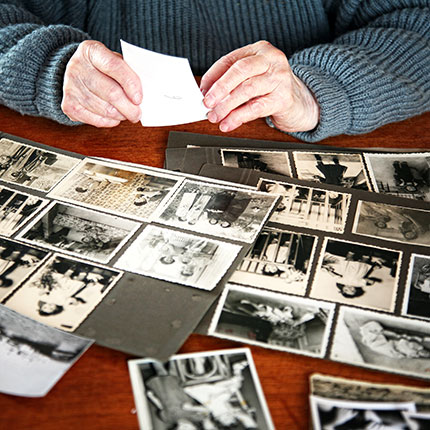 Hands above old family photographs