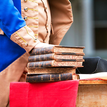 Man dressed as Ben Franklin with hands on books