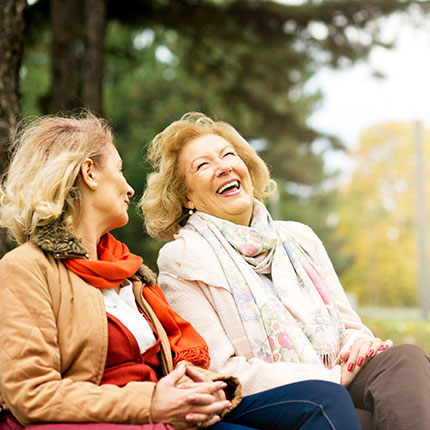 Two older women laughing outside