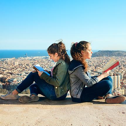 Girls sitting back-to-back, studying