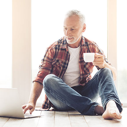 Senior male on laptop with coffee