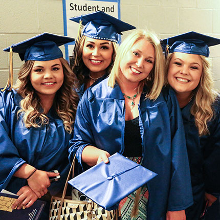 Four female students in caps and gowns on their graduation day