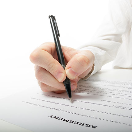 a hand holding a pen and filling out a paper