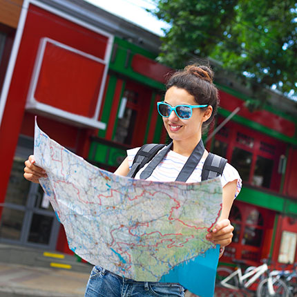 girl with sunglasses reading a map