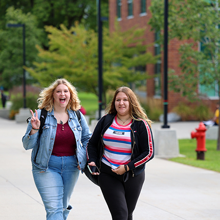Two SFCC students walking on campus smiling into the camera. One is making the peace sign with her right hand.