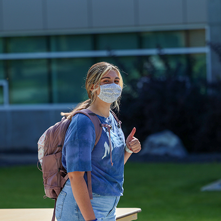 A female SFCC student wearing a facemask and making a thumbs up with her left hand.