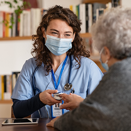A female nurse wearing a mask is checking the blood pressure of an older woman.