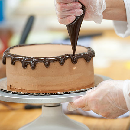 A close up of a student applying dark colored frosting to a brown cake.