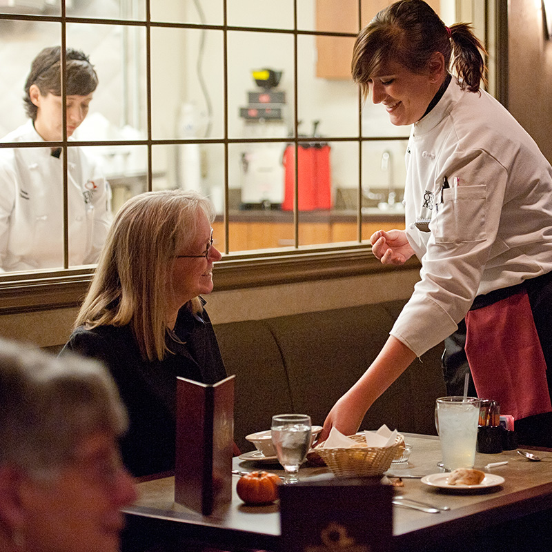 An SCC culinary student in a white chef garb serving food to a woman seated at a table.