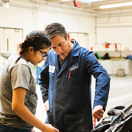 Automotive Student and her Instructor looking at a car