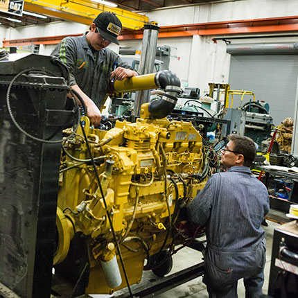 Diesel mechanic students working on an engine.