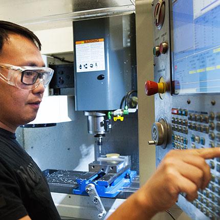 Machining student program a CNC machine.