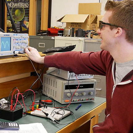 Electronics student working with equipment.